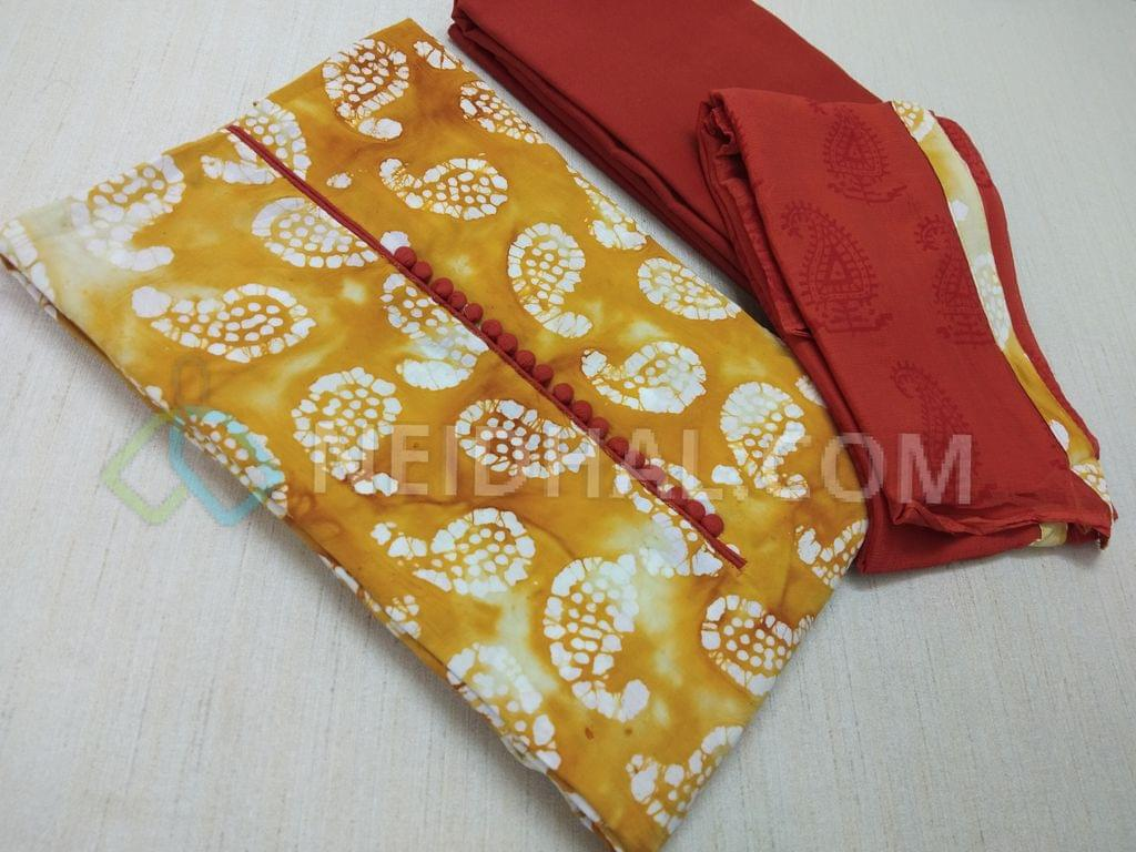 Premium Yellow Cotton unstitched salwar material with potli buttons, Real Batik Bandhini work on both sides, Light Brick Red cotton bottom, Block printed light Brick Red chiffon dupatta with taping.