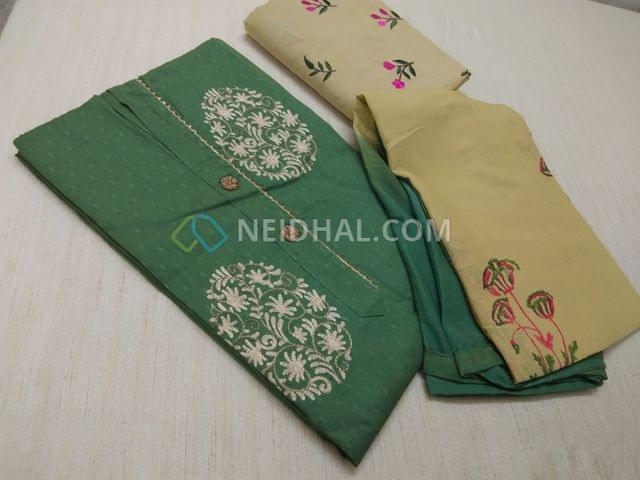 Green unstitched salwar material with fancy button and embroidery work on yoke, embroidery work on beige cotton bottom, block printed work chiffon dupatta with taping