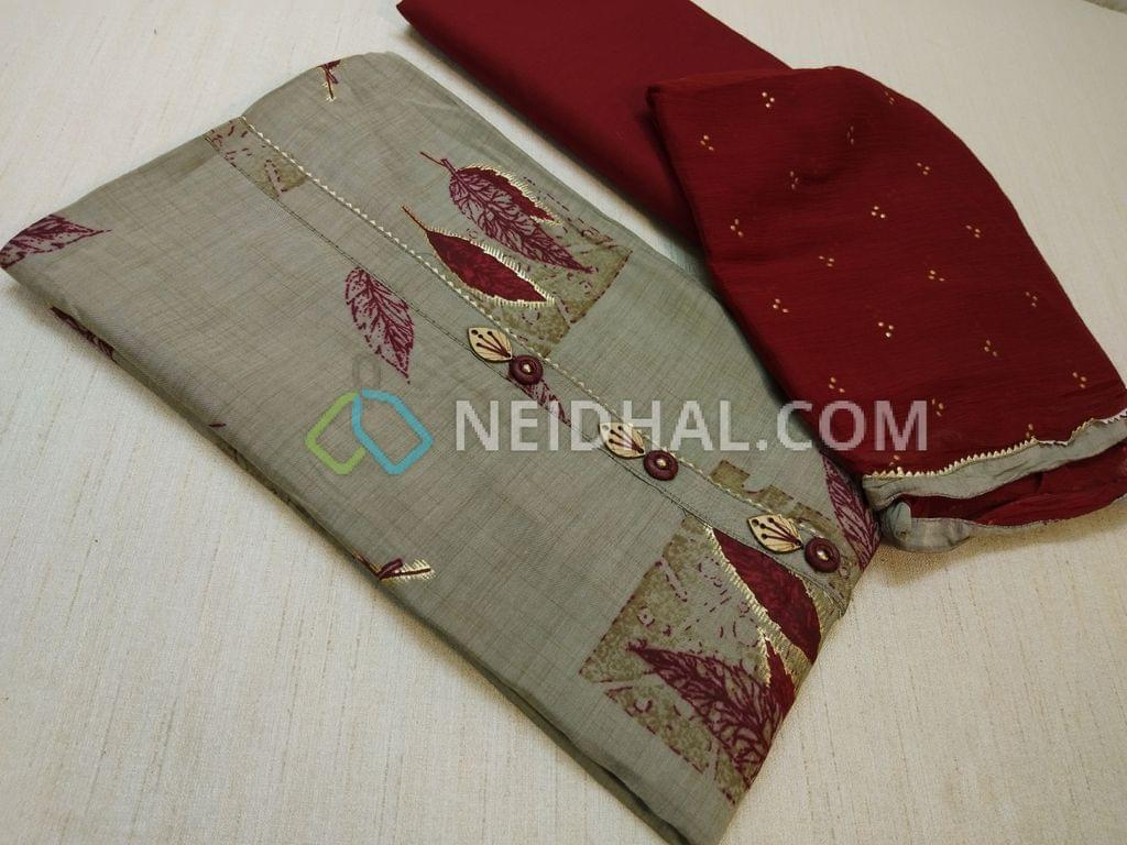 Grey Printed Semi Masleen Silk unstitched salwar material( thin and soft fabric requires lining) with fancy buttons on yoke, Maroon cotton bottom, Maroon Chiffon dupatta with dew drops work and taping.