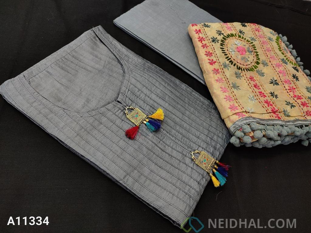 CODE A11334 : Designer Grey Silk Cotton unstitched Salwar material(requires lining) with pintuk work on front side, stitched round neck, Metal tassels on yoke, Grey Cotton bottom, Heavy Kantha stitch and stem stich work on Golden Beige silk cotton dupatta with pom pom tapings.