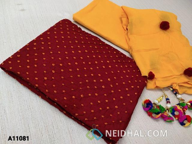 CODE A11081 : Designer Maroonish Red pure Cotton Bandhini unstitched Salwar material(requires lining, ) with hand made tie and dye bandhini work,  bright yellow cotto bottom, pom pom works on yellow chiffon dupatta with fancy tassels