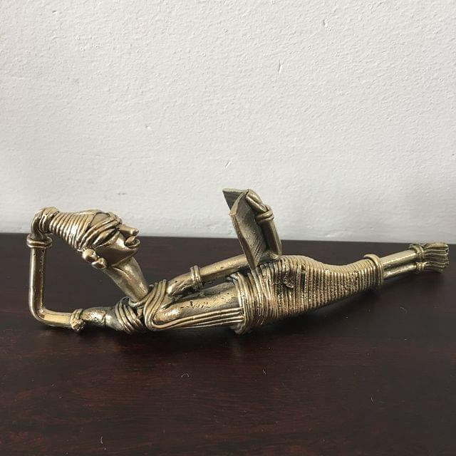 Dhokra - Tribal Woman lying on side and reading book